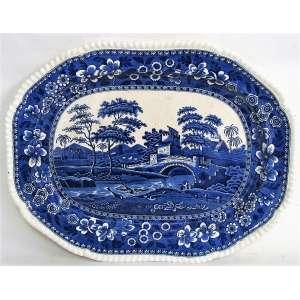 Travessa em faiança inglesa profusamente decorada em tons de azul, com cena de paisagem com pássaros, figuras e casas. Borda trabalhada em gomos. arca da manufatura no verso. Med. 4x48,5x37,5cm.