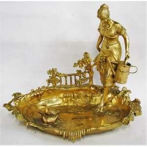 Belo centro de mesa em metal banhado de dourado, com influencia Art-Noveau, na forma de lago com patinhos, e adornado com figura de camponesa com balde. (dourado com estofados devido ao desgaste do tempo). Med. 31x38x25cm.