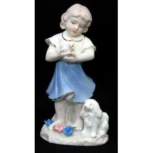 Estatueta figurando menina, pássaro e cãozinho em porcelana estilo Lladró. Delicada policromia e modelagem floral manual. Importado. Medidas: 15x8 cm.