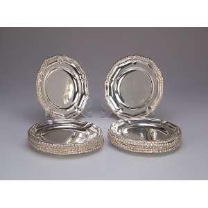 Conjunto de 12 porta-copos de prata repuxada, borda recortada em godrons. 14 cm de diâmetro. Marca do teor 833 e do fabricante Adriano.<br>Brasil, séc. XX.